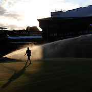 LONDON, ENGLAND - JULY 13:  Ground staff watering the outer courts with the back drop of Center Court at the end of the days play during the Wimbledon Lawn Tennis Championships at the All England Lawn Tennis and Croquet Club at Wimbledon on July 13, 2017 in London, England. (Photo by Tim Clayton/Corbis via Getty Images)