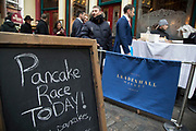 Free pancakes on Shrove Tuesday as festivities warm up for the Leadenhall Market Pancake Day Race on 13th February 2018 in London, United Kingdom. Competing teams of City workers outside The Lamb Tavern tackle the 25m course, competing to win the coveted frying pan trophy as they flip their way around the historic 14th century market.