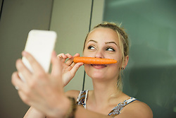 Young woman taking a selfie and making moustache with a carrot on her face, Munich, Bavaria, Germany