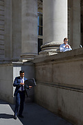 A businessman walks on Threadneedle Street beneath another City worker enjoying a sunlit lunch hour at Royal Exchange Cornhill, in the City of London, the capital's ancient, financial district, on 14th May, in London, England.
