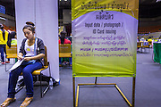 """17 JULY 2014 - BANGKOK, THAILAND:  An undocumented Cambodian woman waits her turn at the temporary """"one stop service center"""" in the Bangkok Youth Center in central Bangkok. Thai immigration officials have opened several temporary """"one stop service centers"""" in Bangkok to register undocumented immigrants and issue them temporary ID cards and work permits. The temporary centers will be open until August 14.   PHOTO BY JACK KURTZ"""