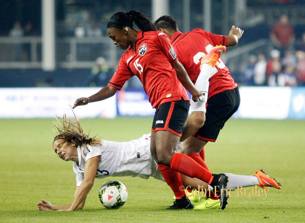 USA's Alex Morgan, bottom gets tripped up by Trinidad's Liana Hinds (15) during the first half of the CONCACAF Women's Championship Wednesday, Oct. 15, 2014, in Kansas City, Kan.(AP Photo/Colin E. Braley)