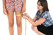 female tailor measures customer with tapemeasure