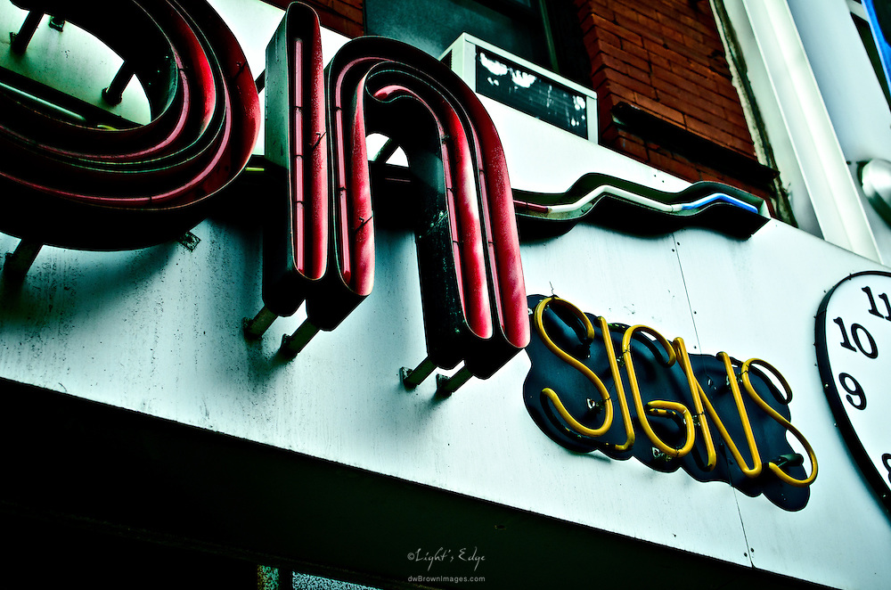 Neon signs above a sign company's shop in NYC.