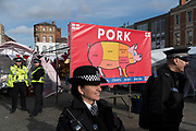 Boston Butt, advertisement for pork meat at Boston Market. Old white vote demographic for Brexit against immigrants with police<br /><br />Boston had the highest proportion of votes for Brexit in mainland UK. Boston in Lincolnshire was once a sleepy rural town. Since early the 21st century a large influx of economic migrants mainly from Eastern Europe have found work across Lincolnshire, working for the minimum wage in agricultural and construction industries, doing jobs that locals don't to do. Towns have expanded sometimes by 10% during this period. British business needs the migrant workers to survive, but but local people voted the highest proportion for Brexit, 75% against 'Remain', in a protest vote against migrant workers.
