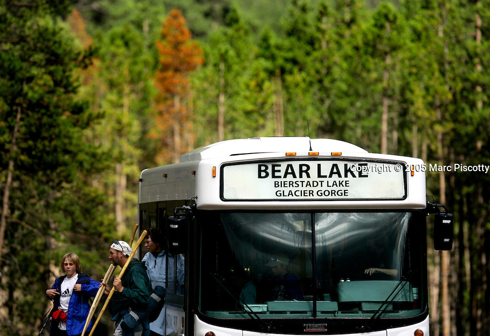 Park goers exit a shuttle bus at the Park and Ride at Rocky Mountain National Park on Thursday August 18, 2005. The park, open since 1915, is a showcase of the grandeur of the Rocky Mountains and features peaks ranging from 8,000 to 14,259 feet tall and is home to elk, mule deer, bighorn sheep, black bears, coyotes and a wide range of birds, fish and smaller animals. The shuttles and Park and Ride at the park were established to cut down on traffic within the park and lessen congestion on the roads. Rocky Mountain National Park is located in the north-central region of the U.S. state of Colorado..Rocky Mountain National Park features majestic mountain views, a variety of wildlife, varied climates and environments?from wooded forests to mountain tundra?and easy access to back-country trails and campsites. The park is located north-west of Boulder, Colorado in the Colorado Rockies, and includes the Continental Divide and the headwaters of the Colorado River in its land area.Rocky Mountain National Park encompasses approximately 265,770 acres (1,076 km²) of land in Colorado's northern Front Range. The park is split by the Continental Divide, which gives the eastern and western portions of the park a different character. The east side of the park tends to be dryer, with heavily glaciated peaks and cirques. The west side of the park is wetter and more lush, with deep forests dominating..The park contains 359 miles (578 km) of trails, 150 lakes, and 450 miles (720 km) of streams. The park contains over 60 named peaks higher than 12,000 feet (3,700 m), and over one fourth of the park resides above tree line. The highest point of the park is Longs Peak, which rises to 14,259 feet above sea level. Longs Peak is the only fourteen thousand foot peak in the park..(MARC PISCOTTY/ © 2005)