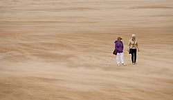 © Licensed to London News Pictures. 12/09/2011..Saltburn Beach, Saltburn, Cleveland, England...A couple walk through gusts of sand as strong winds blow across the beach at Saltburn in Cleveland...Photo credit : Ian Forsyth/LNP