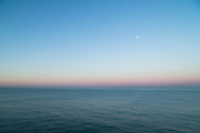 View of sea at sunrise with moon in sky, Cadiz, Andalusia, Spain