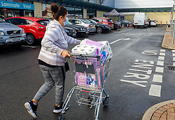 "© Licensed to London News Pictures. 24/09/2020. London, UK. A shopper wearing a face covering pushing a shopping trolley with packs of toilet rolls leaves a supermarket in London, as essential items start to run out, amid new lockdown measures due to a rise in COVID-19 cases. Foreign Secretary, DOMINIC RAAB has said that, a second national lockdown could be needed if the latest coronavirus restrictions do not work but the government will ""take every effort to avoid that"". Photo credit: Dinendra Haria/LNP"
