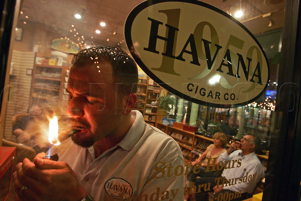 Mike Olivares lights up a cigar at his shop Havana 1959 Cigar Company in Miami Lakes. Mike was reared in Miami Lakes by his Cuban parents Luis and Marissa Olivares, at right. His parents still live in Miami Lakes on September 9, 2006.