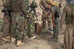 © Licensed to London News Pictures. 11/09/2015. Kirkuk, Iraq. Kurdish peshmerga fighters inspect Islamic State improvised explosive devices near the village of Abo Muhammad. The devices were discovered during an offensive set to expand a safety zone around Kirkuk, Iraq.<br /> <br /> The offensive, which went unchallenged after ISIS left the area ahead of the attack, saw the peshmerga capture 15 villages along the Kirkuk front line. The objective of the offensive was to expand the safety zone around Kirkuk, stopping militants from firing missiles and rockets in to the city of Kirkuk. 3 peshmerga were killed and 24 wounded due to improvised explosive devices left behind by the militants. Photo credit: Matt Cetti-Roberts/LNP