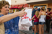01 AUGUST 2012 - CHANDLER, AZ: A woman shows off her bags of take out chicken at a Chick-fil-A Wednesday. Thousands of people stood in line for up to an hour at the Chick-fil-A in Chandler, AZ, a suburb of Phoenix Wednesday after MIKE HUCKABEE, the former governor of Arkansas and Fox News host, called for a national ''Chick-fil-A Appreciation Day,'' a day on which he encouraged people to patronize the fast food chain, this after DAN CATHY, President and CEO of Chick-fil-A, who is a fundamentalist Christian, made public his views against same sex marriage, causing an outcry from political leaders and Gay rights advocates.    PHOTO BY JACK KURTZ