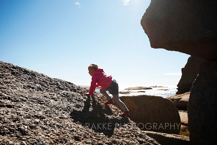 Rakke, Norway. Girl climbing on rock