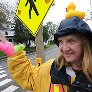 """Lisa Green, crossing guard at the corner of Longfellow and Maine streets in Brunswick, has a wave or a smile for nearly every passerby. Her habit of wearing funny hats began last year when serving near Jordan Acres School.   """"I was clipped,"""" she said, """"and it hurt!""""  The guy {who hit me} kept saying that he didn't see me -- so I decided to start making it impossible to not see me."""" She added, """" My best hats come out at Halloween!""""  Photo by Roger S. Duncan."""