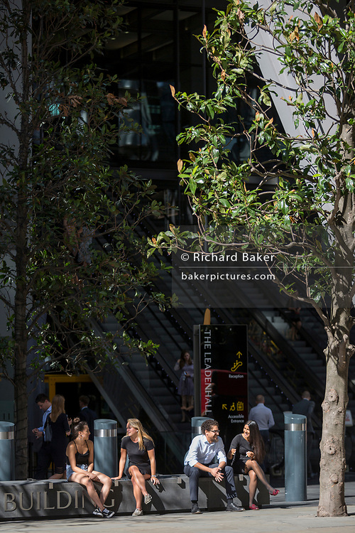 Workers enjoy sunshine outside the Leadenhall Building during the 2018 heatwave in the City of London, the capital's historic financial district, on 2nd August 2018, in London, England.