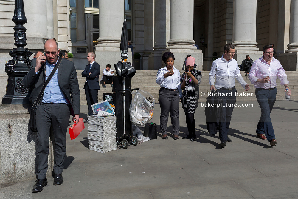 As young women check their phones, a man carried a red box below the classical architecture of Royal Exchange at Bank Triangle, on 10th May 2017, in the City of London, England.
