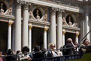 Tourists on the top deck opposite L'Opera during a city tour of Paris, France. Some visitors have guidebooks and maps covering their heads, shading themselves from a hot Parisien sun - while others look down at the street below as they drive the streets of the Paris capital. In the background are the pillars and columns of the Palais Garnier (The Paris Opera). The tour company is Les Cars Rouges, a hop-on, hop-off bus tour of Paris allowing the tourist to explore the city's top tourist attractions from a high, open-top perspective. The Palais Garnier is a 1,979-seat opera house, which was built from 1861 to 1875 for the Paris Opera.
