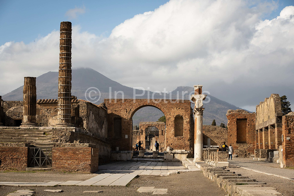 Figures are silhouetted in an archway in the Forum at the Pompeii Archeological Park on Friday 6th March 2020 in Pompei, Italy. Park officials estimate that visitor numbers are down to a sixth of what they would normally be as a result of the spread of Coronavirus, which has prompted the closure of all Italian schools and universities, and the postponing of many sporting events. .
