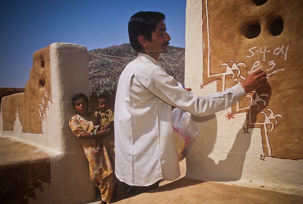 Some fifteen km' from the village Khuri in Jaisalmer district, Health workers go 'door-to-door' to immunize children. Individual houses are then marked with chalk, indicating that they all have been covered.