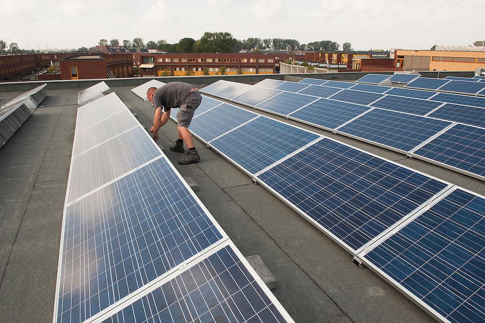 Nederland, Nijmegen, 23 aug 2012.Aanleg zonnepanelen op het dak van een gebouw.Montage pv panelen.Foto(c): Michiel Wijnbergh
