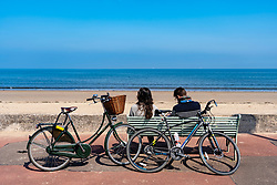 Portobello, Scotland, UK. 25 April 2020. Views of people outdoors on Saturday afternoon on the beach and promenade at Portobello, Edinburgh. Good weather has brought more people outdoors walking and cycling. Police are patrolling in vehicles but not stopping because most people seem to be observing social distancing. young couple with bicycles resting on a bench.  Iain Masterton/Alamy Live News