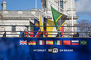 A tour bus with international flags passes larger flags of the Commonwealth that are flying in Parliament Square on the occasion of Commonwealth Day, on 11th March 2019, in London, England.