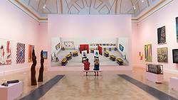 "© Licensed to London News Pictures. 05/06/2018. LONDON, UK. Staff members view ""Seven Trollies, Six and a Half Stools, Six Portraits, Eleven Paintings and Two Curtains"" by David Hockney RA at a preview of the 250th Summer Exhibition at the Royal Academy of Arts in Piccadilly, which has been co-ordinated by Grayson Perry RA this year.  Running concurrently, is The Great Spectacle, featuring highlights from the past 250 years.  Both shows run 12 June to 19 August 2018.  Photo credit: Stephen Chung/LNP"
