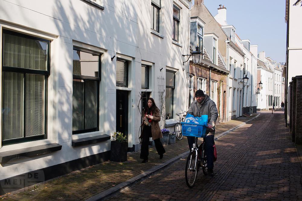 Een voetganger en fietser in de Walsteeg in Utrecht.<br /> <br /> A pedestrian and cyclist the Walsteeg in Utrecht.