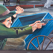 A pedestrian seemingly walks into aim walking by a mural in Belfast, Northern, Ireland.  - Leica 240 MP / 135 mm