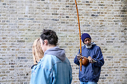 On the South Bank in London a busker plays a berimbau, a traditional African/Brazilian instrument.