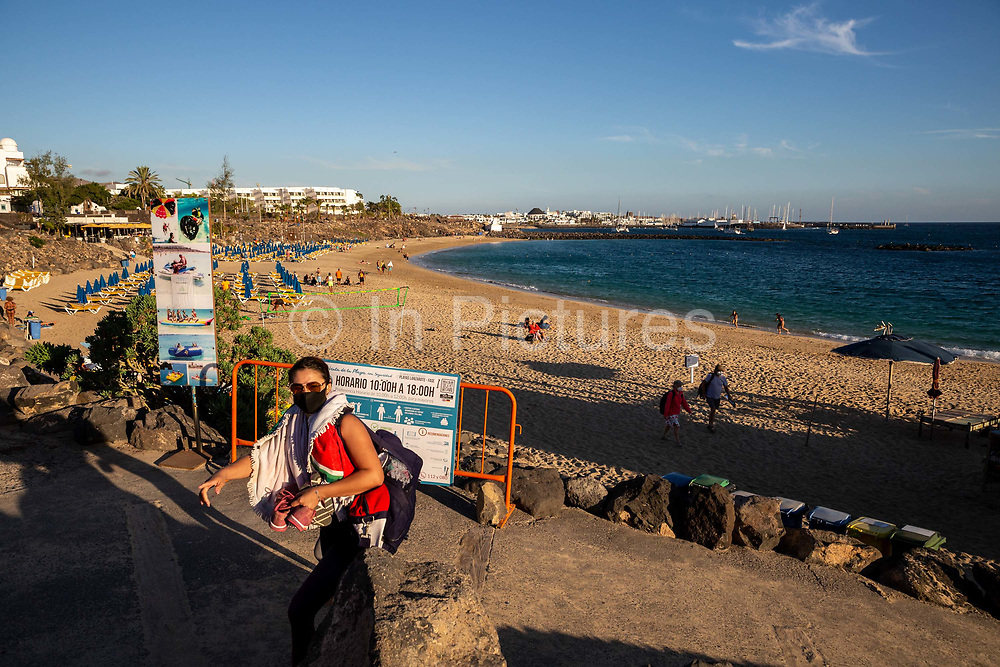 A woman in a face mask walks in front of a quiet beach at Playa Dorada in Lanzarote, Spain on 22nd November 2020. Beaches and resorts across the island are nearly deserted since tourism plummeted due to Covid restrictions elsewhere in Europe. Although the Canary Islands have been relatively unscathed by the virus, with 155 lives lost from 2.1 million residents, the region is heavily dependent on tourism and locals are hoping that numbers recover as lockdown measures ease and vaccines potentially reduce the numbers of infections.
