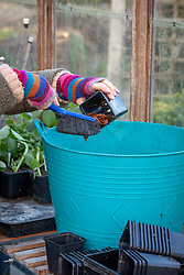 Clearing out old plastic pots with a brush at the end of winter ready for re-use
