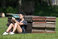© Licensed to London News Pictures. 02/06/2021. London, UK. A woman relaxes during sunny weather in Green Park in Central London. Temperatures are expected to rise with highs of 28 degrees forecasted for parts of London and South East England today . Photo credit: George Cracknell Wright/LNP