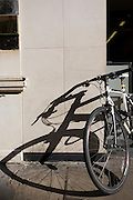 A courier's mountain bike rests on a Bond Street wall, its distorted shadow on an off- white wall.