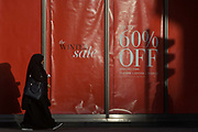 Sale reductions at a branch of UK retailer Marks & Spencer, on Bishopsgate in the City of London. With the shadow of a nearby traffic light, a Muslim lady consumer walks towards a banner announcing the new post-Christmas winter sale offering up to 60% reductions on clothing. Marks & Spencer has over the last 129 years grown from a single market stall to become an international multi-channel retailer, now operating in over 50 territories worldwide and employing almost 82,000 people.
