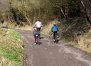 Man and children cycling up a track, Cherhill, Wiltshire, England, UK