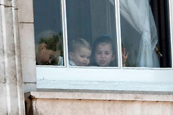 © Licensed to London News Pictures. 08/06/2019. London, UK. Prince George, Prince Louis, Princess Charlotte look through a  Buckingham Palace window during the Trooping the Colour ceremony to mark Queen Elizabeth II's 93rd birthday. Photo credit: Ray Tang/LNP
