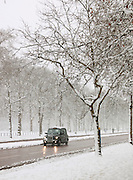 A London Black taxi cab driving down the Mall, covered in snow in London, UK