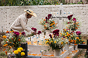An elderly man decorates the gravesite of his son with marigolds, red cockscomb and offerings for the Day of the Dead festival October 31, 2017 in Tzintzuntzan, Michoacan, Mexico.
