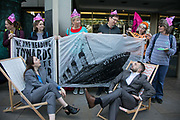 Extinction Rebellion activists target the International Maritime Organisation Climate Conference and delegates, May 13th 2019, in London, United Kingdom. The activists handed out pink XR biscuits, a string ensemble played and a couple were busy re-arranging the deck chairs, all a play on the sinking Titanic. Everyone were playing the part, pretending everything will be fine inspite of the threat of climate break down. The actvists want the the shipping indurstry to take on board that climate change is real and that the industry needs to do more to cut emmissions. The environmental protest group Extinction Rebellion has called for civil disobedience and peaceful protest to force the British government to take drastic action on climate change. The group wants the governenmet to tell the truth and admit that the impact of climate change is much more severe than they say and that action to mitigate catastrophic climate change is urgent.