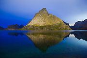 A mountain glows at night, lit by the lights of nearby Reine, Moskenesoya, Lofoten Islands, Norway.