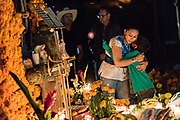 A woman hugs a young boy at the gravesite of a family member during the Day of the Dead festival October 31, 2017 in Tzintzuntzan, Michoacan, Mexico.