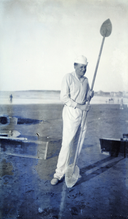 male person standing on the beach holding a kayak paddle 1920s