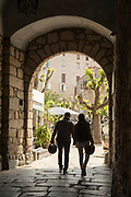 Couple carrying motorcycle helmets walking under arch, Corte, Corsica, France
