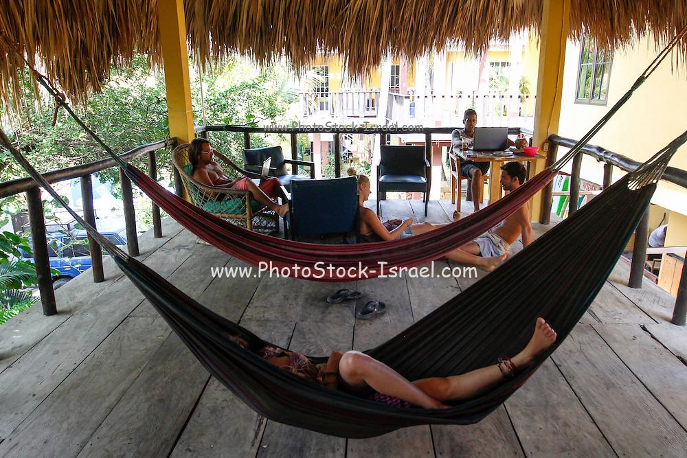Group of European tourists resting on hammocks. Photographed at El Tunco beach, El Salvador,