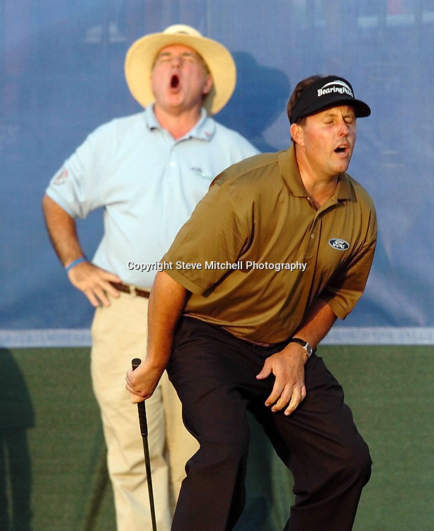 Phil Mickelson flinches in agony after missing the putt on the 18th green that would have tied the score with Tiger Woods Sunday, March 6, 2005 at the Ford Championship at Doral in Doral, Fla. Woods won with a score of 24 under parr, one shot better than Mickelson. (Photo/Steve Mitchell)
