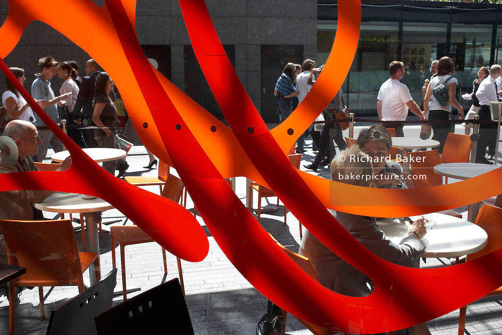 Office workers mingle and chat in warm late-summer sunshine during a lunchtime break at More London, Southwark.
