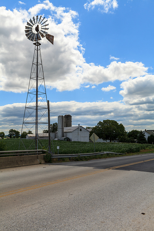 Ephrata, PA, USA- June 26, 2012: A Lancaster County farm with cornfield and wind mill on a sunny day in early summer.