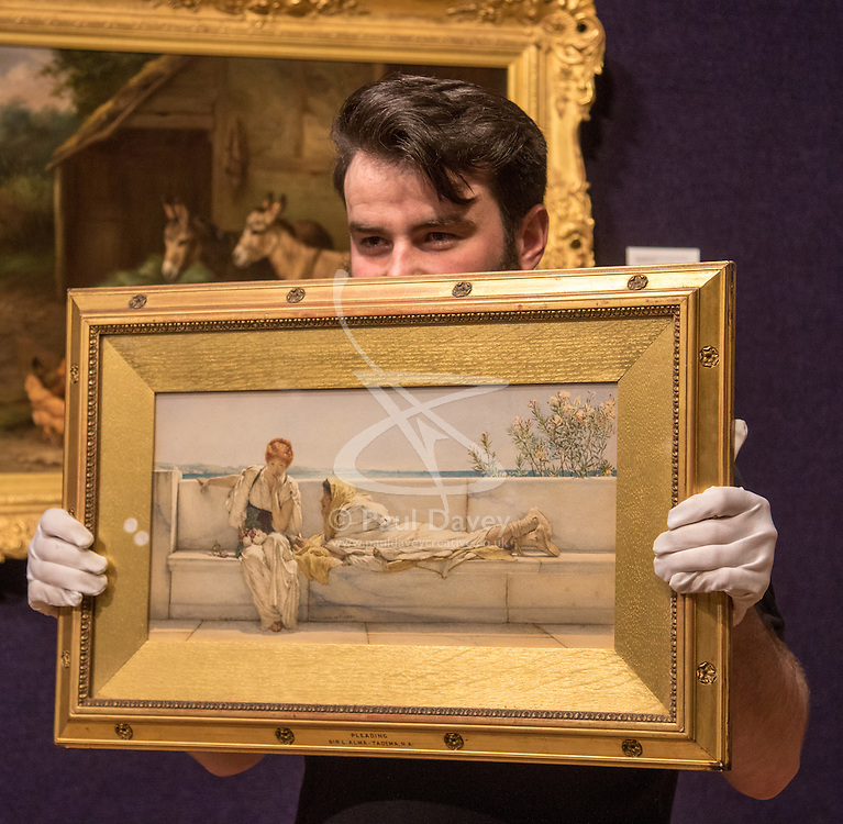 Bonhams, London, February 22nd 2017. Bonhams in London hold a press preview ahead of their 19th century paintings sale, featuring numerous valuable works including:<br /> • 'Children by the shore' by Dorothea Sharp, valued at £60,000-80,000<br /> • Barcas y pescaadores, Playa de Valencia by Joaquin Sorolla £60,000-80,000<br /> • When the Boats Come In by Walter Osborne valued at £100,000-150,000<br /> • A Solicitation by Lawrence Alma-Tadema which is expected to fetch between £30,000-50,000<br /> PICTURED: A Bonhams galley porter prepares to hang A Solicitation by Lawrence Alma-Tadema