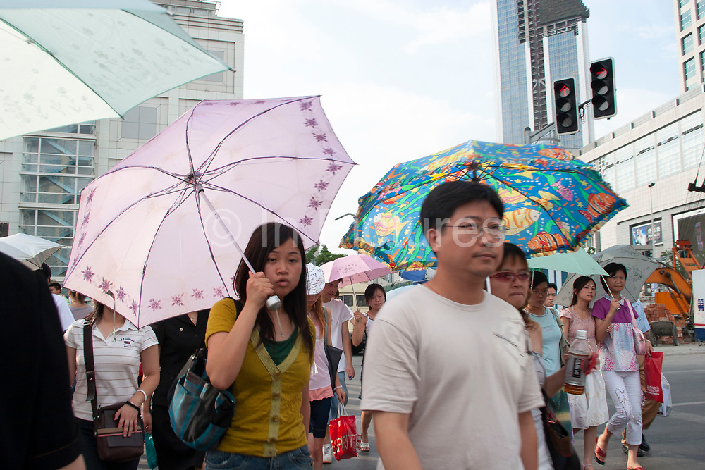 Young Shanghainese shield themselves from the sun with umbrellas as they cross the road at the busy junction next to the Shanghai Urban Planning Museum in Shanghai, China. This area at the edge of People's Square, and at one of the main exits for People's Square Metro is one of Shanghai's busiest places in the heart of the downtown area. Young Chinese women tend to shield themselves from the sun to keep their skin lighter as western skin-tones are highly desired.